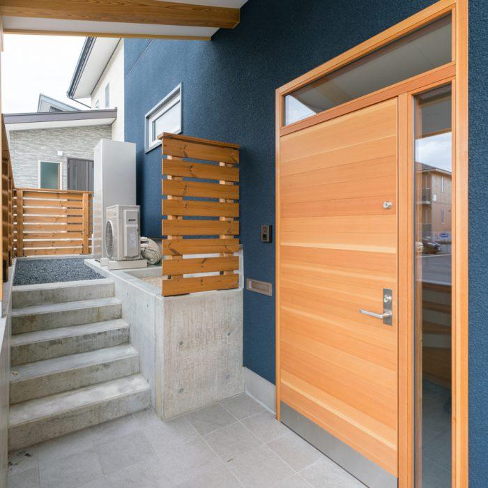 木製の玄関ドア。階段を上がり奥へ進むと庭へ続きます。